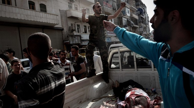 An opposition fighter shouts for help as he delivers the body of a civilian who was wounded during shelling by Syrian government forces outside a hospital in Syria's northern city of Aleppo AFP PHOTO / ARIS MESSINIS