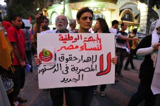 """A supporter of the National Front for Egyptian Women joins a march from Talaat Harb Square holding a sign that says """"no to wasting women's rights in the new constitution"""" Hassan Ibrahim / DNE"""