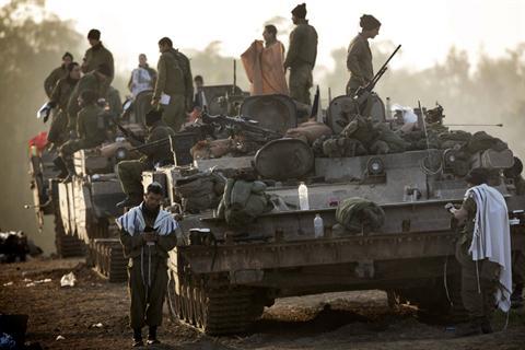 "sraeli soldiers wearing ""Talit"" (prayer shawls) conduct morning prayers at an Israeli army deployment area near the Israel-Gaza Strip border on 20 November. (AFP PHOTO / MENAHEM KAHANA)"
