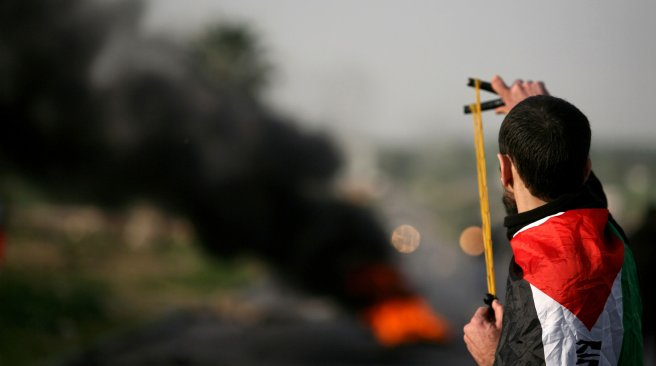 A Palestinian protestor aims his slingshot at Israeli police during clashes at the entrance of the Jalama checkpoint, near the West Bank city of Jenin, on February 22, 2013. AFP PHOTO