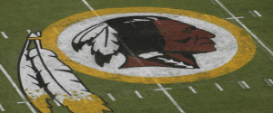 In this photo taken Aug. 7, 2014, the Washington Redskins logo is seen on the field before an NFL football preseason game against the New England Patriots in Landover, Md. Lawyers for the Washington Redskins are telling a judge that the team's free-speech rights are being infringed by a federal panel's decision to cancel the team's trademarks for being disparaging to Native Americans. (AP Photo/Alex Brandon)