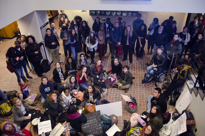 Student protesters sit in the lobby of Crouse-Hinds Hall shortly after entering the building on Monday afternoon. The students slept over in Crouse-Hinds on Monday night and plan to stay until at least Thursday.