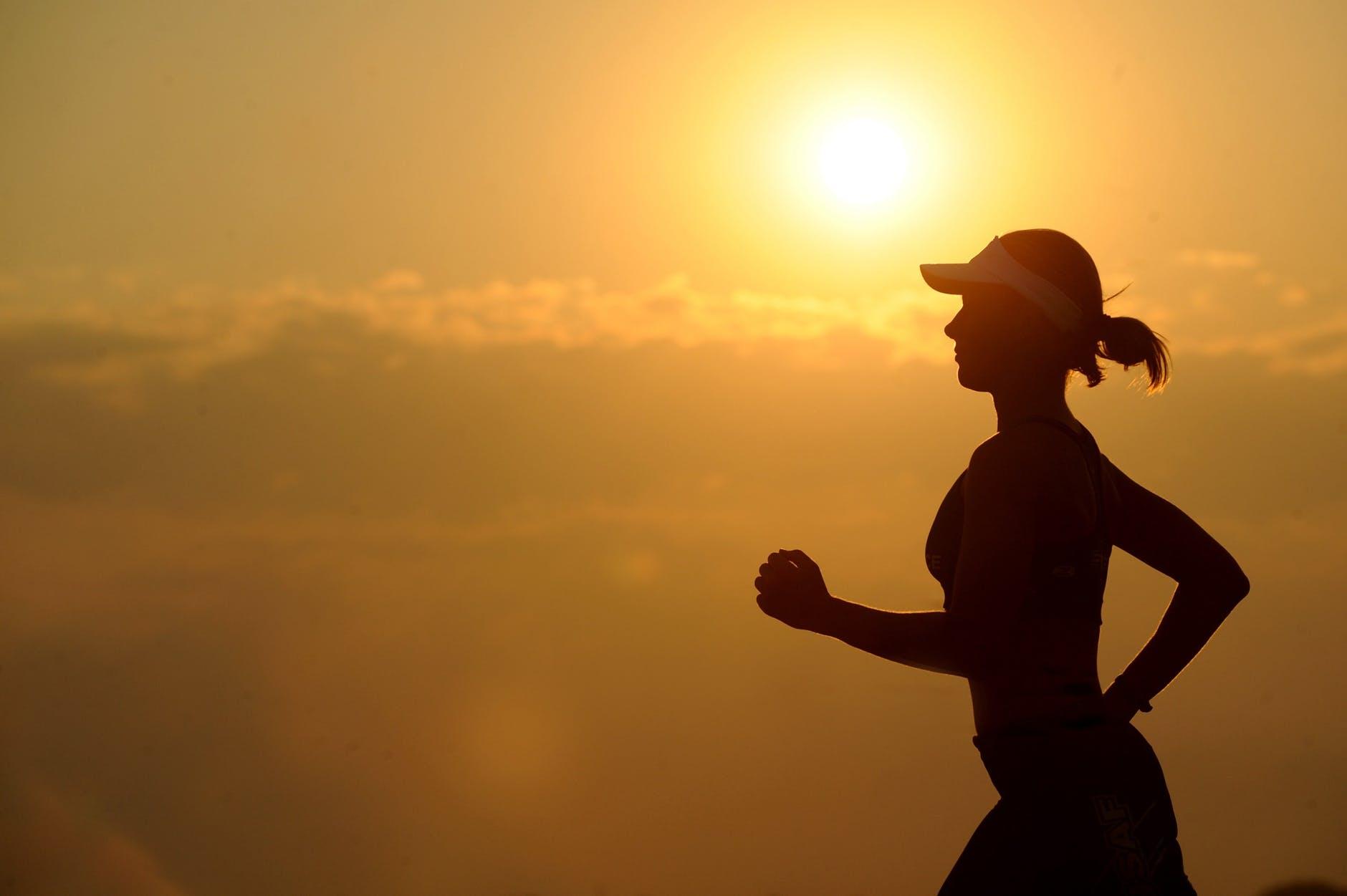 woman with white sunvisor running