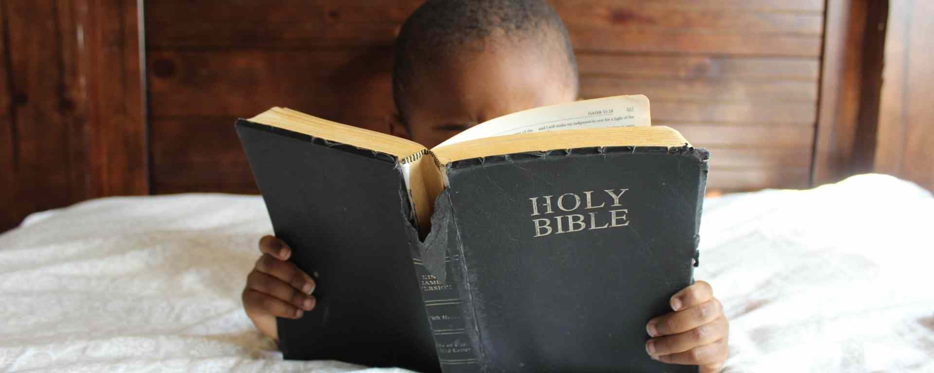 Young Child sitting in bed reading the bible.