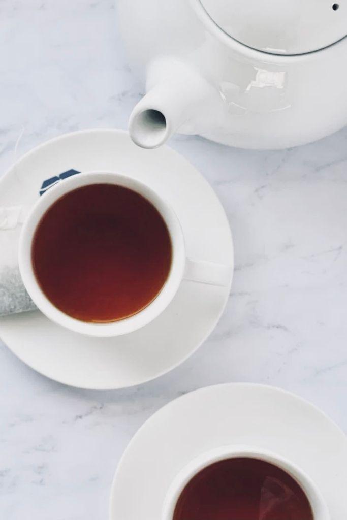 tea in teacups with teapot