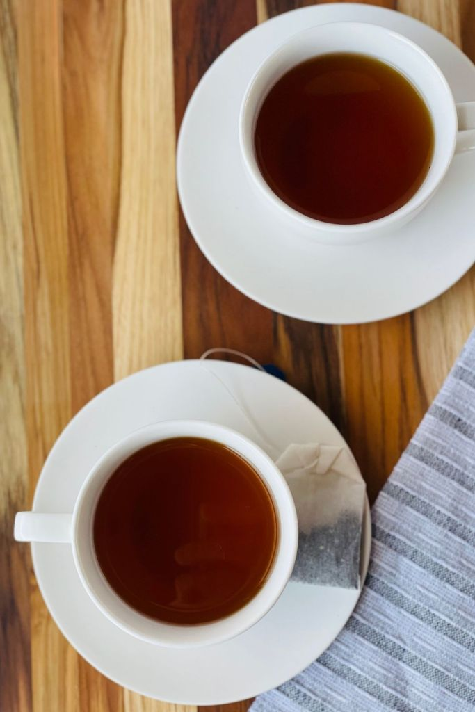 lady grey tea in teacups with teabag on wooden board