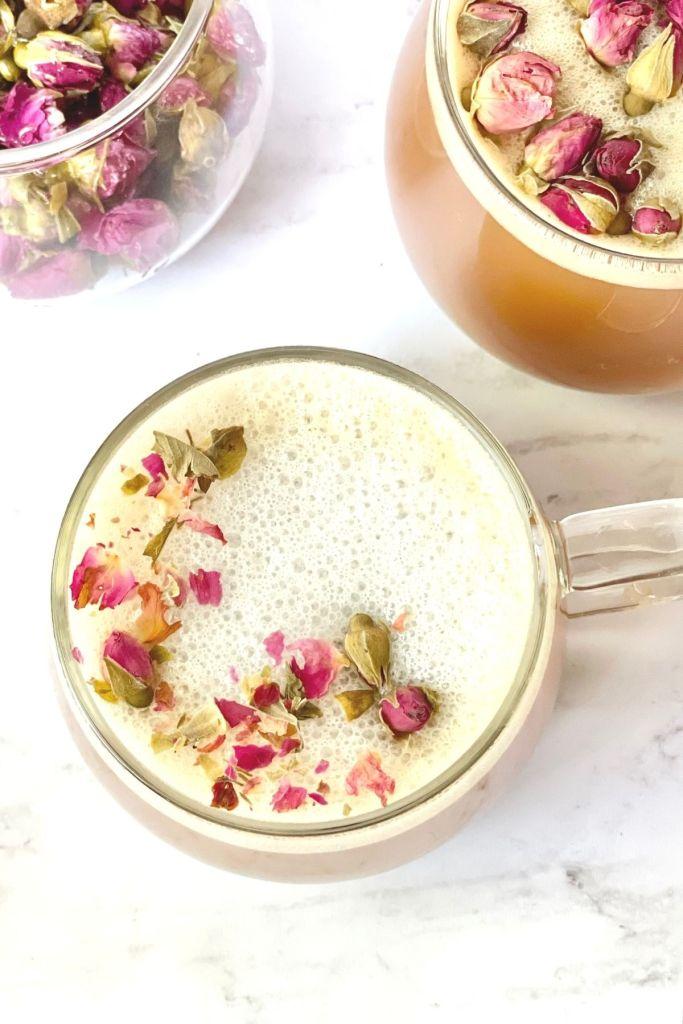 2 tea cups of rose milk tea and a tea cup of rose buds