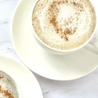 chai tea latte in tea cup with foamy milk and cinnamon