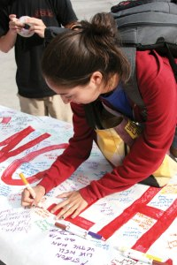 Trojan family · Kathleen Fletes, a senior majoring in psychology, writes a message on a banner for injured running back Stafon Johnson in front of Tommy Trojan Tuesday. - Mike Lee | Daily Trojan