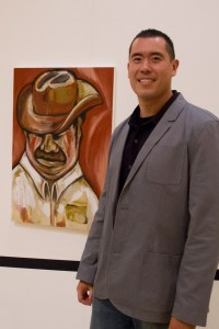 """Hidden talent · Sergeant Rick Gonzales poses next to his painting, """"The Mexican,"""" at the art exhibit """"Beyond the Badge"""" in the Galen Center. - Austin Vogel 
