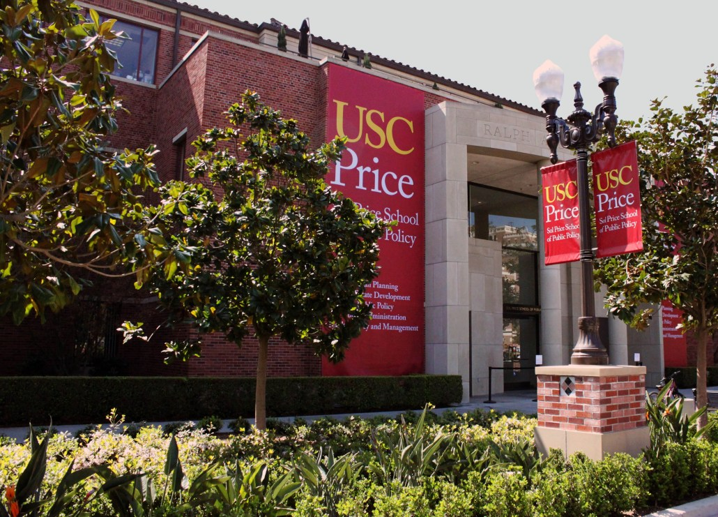 Side angle photo of Sol Price School of Public Policy, a large red brick building with high glass windows. Red banners displaying the school's name hang near the entrance and a lamppost. Green foliage surrounds the premises.