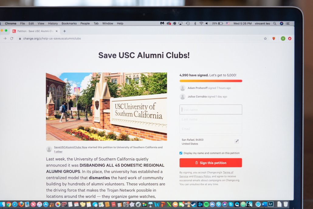 "Photo of the change.org petition created by USC Regional Alumni Group Leadership calling for USC and the USC Alumni Association to reverse the new model and reinstate alumni clubs. The photo displays a portion of a Macbook Air screen and shows more than 4,500 signatures and ""Save USC Alumni Clubs"" in bold above a picture of an entrance to the USC Village, with a student with a gray backpack walking past."