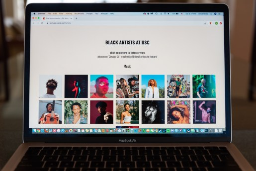 "A Macbook Air screen displays a tab on the USC Black Lives Matter Resources page of ""Black Artists AT USC,"" with lettering at the top of the page. Two rows on the screen depict pictured squares of Black artists engaging in their medium or posing for the photo."
