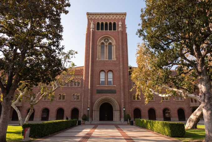 This is a wide angle photo of Board Auditorium on a bright sunny day. The center of Bovard is flanked by tall trees in Alumni Park.