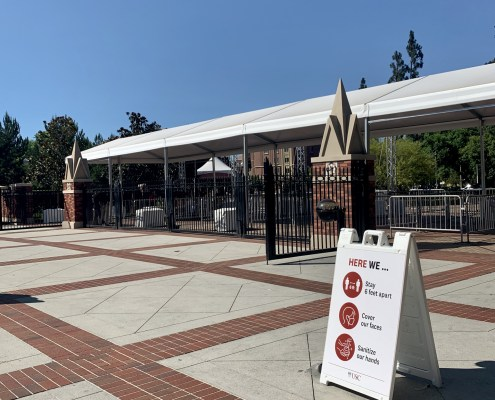 In front of one of the entrances to the campus, a COVID-19 check-in awaits visitors. There is also a white sign urging people to social distance, wear a mask and sanitize regularly.