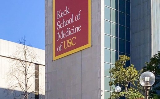 "Photo of the Keck School of Medicine, a tall gray building with a banner reading ""Keck School of Medicine of USC."" There are stairs leading up to the building, surrounding foliage, another building, and a blue sky in the background."