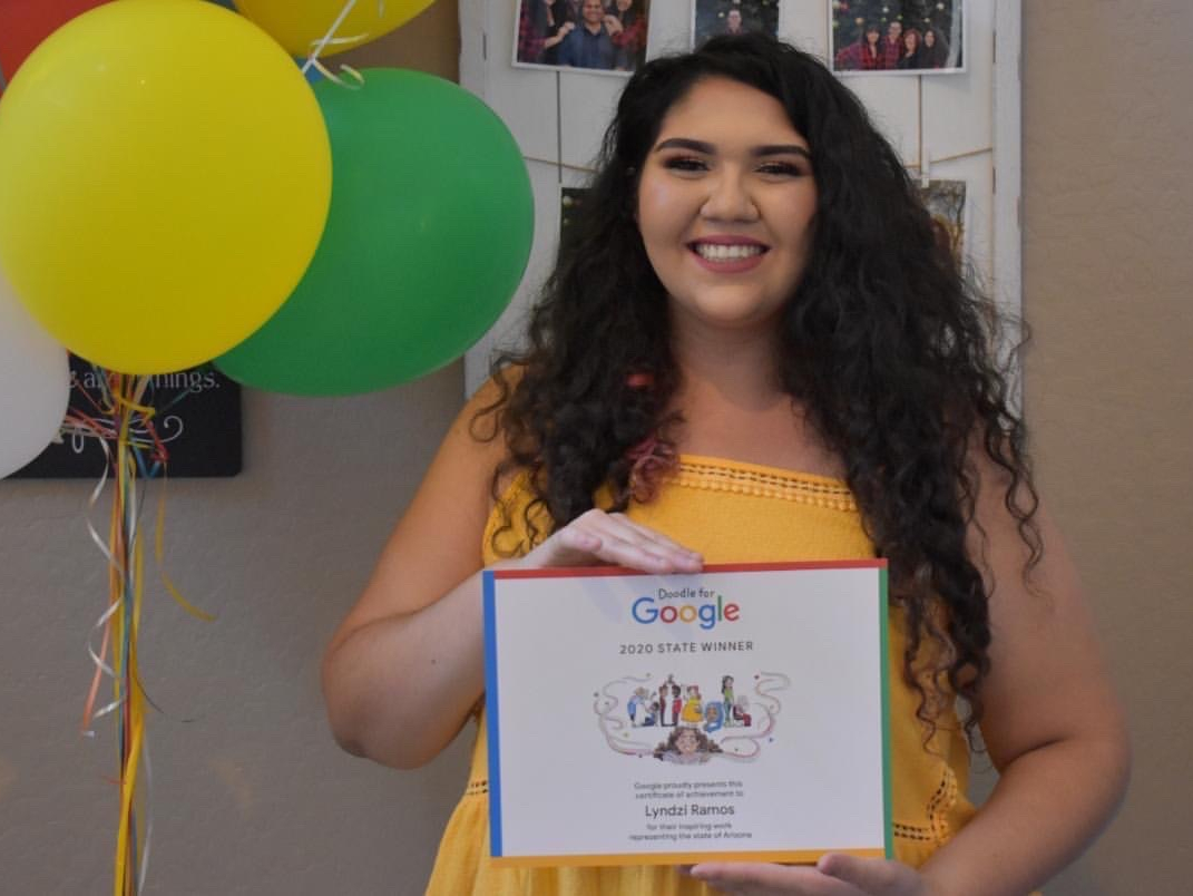 Ramos smiles in front of a balloon bouquet Google gifted her and holds her winning drawing.