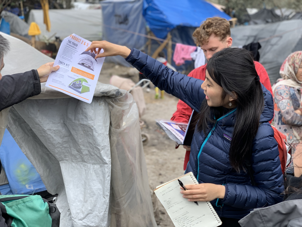 A picture of Lauren Yen pointing to a packet of paper, with the page showing two images of tents and 'The Torch' and 'Torch Kit' shown with the largest lettering. Yen wears a blue parka, with the people surrounding her wearing clothes for warm weather. Various tents are in the background.
