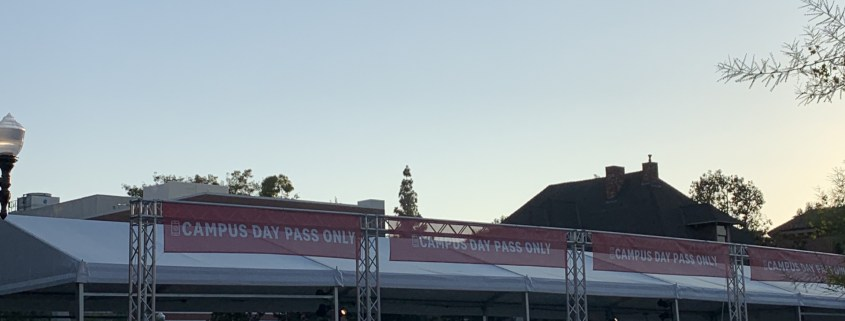 """Photo of an entrance to USC campus with gates, white tents, and red banners that read """"campus day pass only."""""""