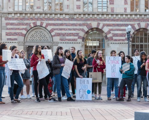 A group of students stand in front of the red brick building of student union holding banners