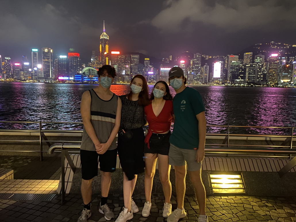 Picture of four students posing in front of a waterbank overseeing the Hong Kong skyline. The students are also wearing blue disposable masks.
