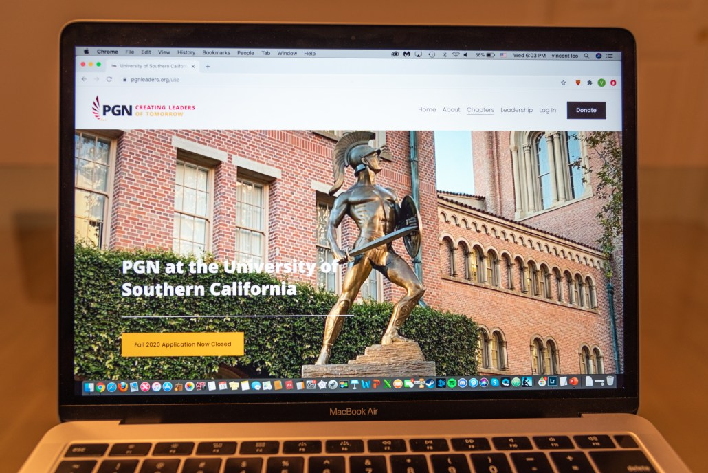A laptop with the PGN website showing a photo of Tommy trojan