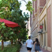 Backs of two people walking in the USC village with red brick building to their left and plants and trees to the right.