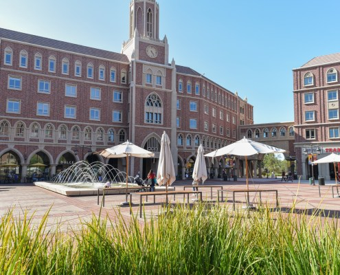 Photo of the red brick buildings of the USC village with green grass at the bottom of the image