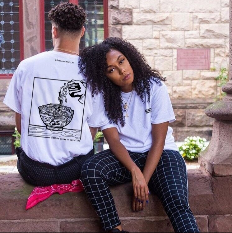 """Two people side by side, the one to the left is turned around to show the back of shirt which has a ramen bowl with depictions of COVID on it, saying """"WHO is going to save US?"""" on the bottom."""