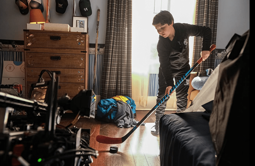 A young boy practicing hockey in his room.