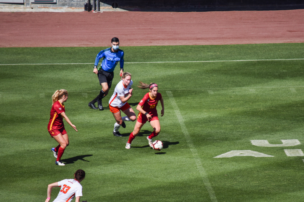Senior midfielder Savannah DeMelo charges ahead of two defenders with the ball at her feet.