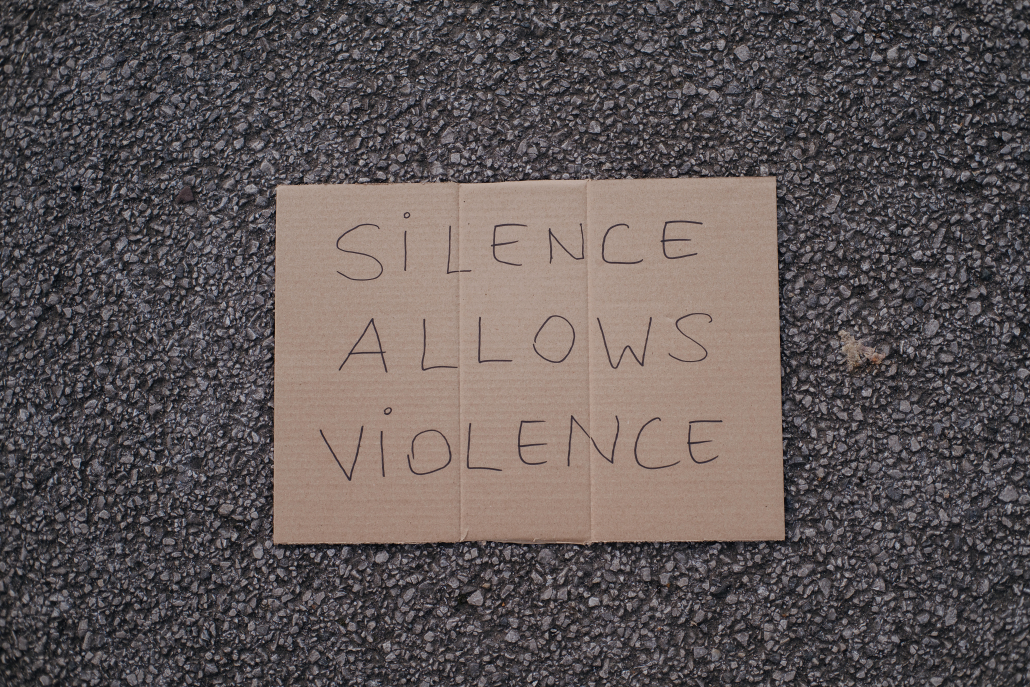 """Cardboard sign that says """"SILENCE ALLOWS VIOLENCE."""""""