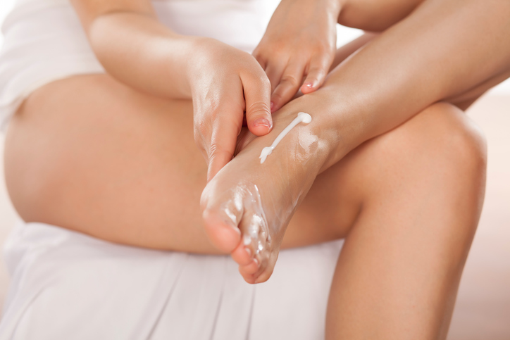 woman applying lotion on feet