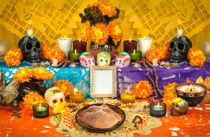 Traditional mexican Day of the dead altar with sugar skulls and candles