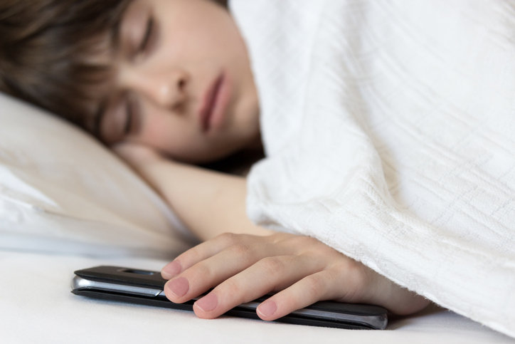 teen in bed with cell