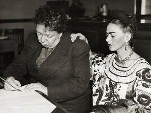 Frida Kahlo places her hand on Diego Rivera's shoulder as he signs paperwork in a black and white photo