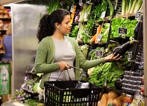Woman looks at an eggplant in the supermarket