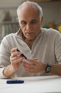 Middle aged man pokes finger to check glucose levels
