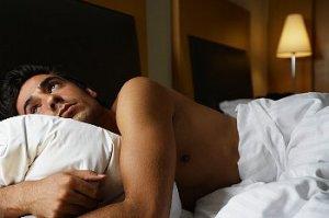 Man lays in bed awake