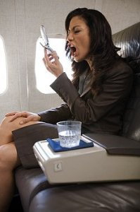 A woman sits in a plane seat yelling at her cell phone