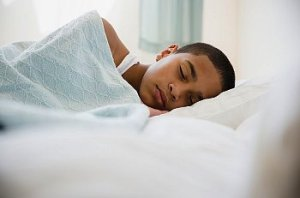 Young boy sleeps under light colored blankets
