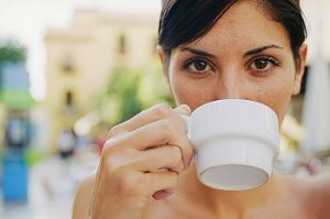 Woman holds white coffee mug up to her face.