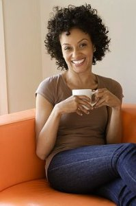 Curly haired woman sits on orange couch with coffee cup