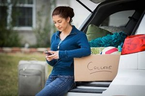 Girl texts while standing against a full van ready for college