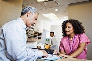 A nurse in pink scrubs talks to patient