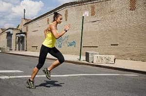 Woman in yellow tanktop running with urban background