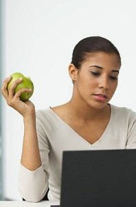 A woman sits at her laptop holding a piece of fruit