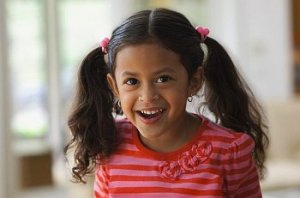 Little girl in pigtails smiles at the camera