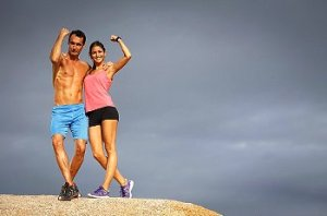 Man and woman stand on top of hill in successful workout