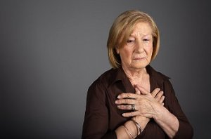 An older woman stands with hands over chest on gray background